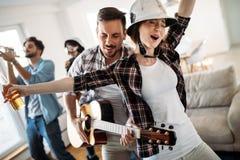Amis gais ayant la partie ensemble et jouant des instruments Image libre de droits