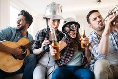 Amis gais ayant la partie ensemble et jouant des instruments Photos stock