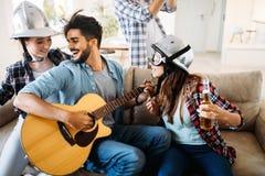 Amis gais ayant la partie ensemble et jouant des instruments Photos libres de droits