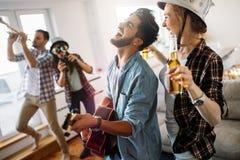 Amis gais ayant la partie ensemble et jouant des instruments Image stock