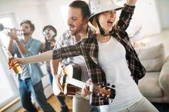 Amis gais ayant la partie ensemble et jouant des instruments Photographie stock libre de droits