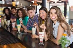 Amis gais ayant le smoothie au restaurant Images stock