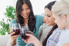 Amis gais ayant le vin rouge ensemble Photographie stock