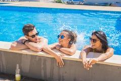 Amis gais buvant des cocktails dans la piscine Photos stock