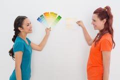 Amis gais choisissant la couleur pour peindre une salle Image stock