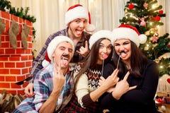 Amis gais dans des chapeaux Santa Claus à Noël, laug de nouvelle année Photos stock