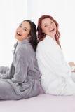 Amis gais dans des peignoirs se reposant de nouveau au dos sur le lit Photos libres de droits
