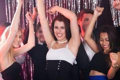 Amis gais dansant dans la boîte de nuit Photo stock