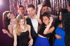 Amis gais dansant dans la boîte de nuit Photos stock