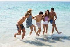 Amis gais dansant en mer Photos stock