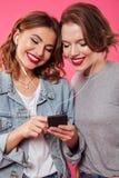 Amis gais de femmes employant la musique de écoute de téléphone portable Image stock