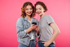 Amis gais de femmes employant la musique de écoute de téléphone portable Photo stock