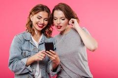 Amis gais de femmes employant la musique de écoute de téléphone portable Images stock