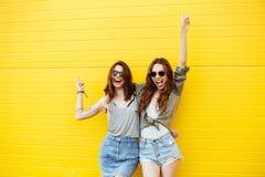 Amis gais de femmes se tenant au-dessus du mur jaune Photos libres de droits