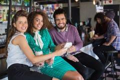 Amis gais discutant au-dessus du mobile tout en ayant la boisson dans le restaurant Photos stock
