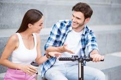 Amis gais discutant le scooter Image libre de droits