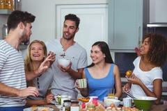 Amis gais discutant tout en prenant le petit déjeuner Image libre de droits
