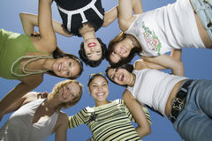 Amis gais formant le petit groupe contre le ciel bleu Photos libres de droits
