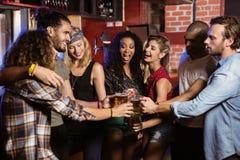 Amis gais grillant des verres de bière Photo stock