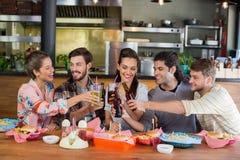 Amis gais grillant la bière tout en se reposant dans le restaurant Photos stock