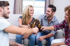 Amis gais grillant la bière tout en se reposant sur le sofa Photographie stock libre de droits