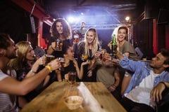Amis gais grillant la boisson à la table avec l'interprète chantant sur l'étape Photo stock