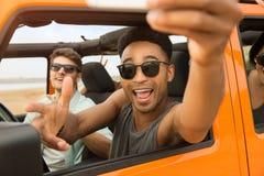 Amis gais heureux prenant un selfie Image stock