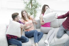 Amis gais jouant avec les oreillers se reposant sur le divan Image libre de droits
