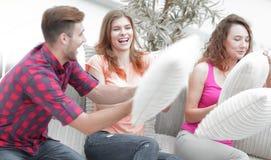 Amis gais jouant avec les oreillers se reposant sur le divan Images libres de droits