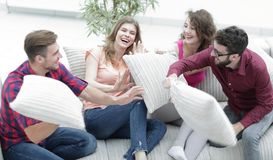 Amis gais jouant avec les oreillers se reposant sur le divan Photos libres de droits
