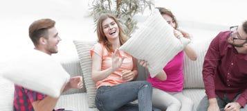 Amis gais jouant avec les oreillers se reposant sur le divan Photos stock