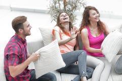 Amis gais jouant avec les oreillers se reposant sur le divan Images stock