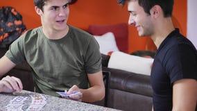 Amis gais jouant des cartes Images stock