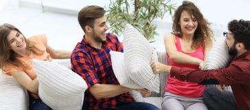 Amis gais jouant le combat d'oreiller, se reposant sur le divan Photographie stock libre de droits