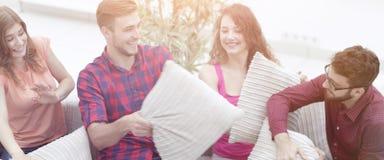 Amis gais jouant le combat d'oreiller, se reposant sur le divan Photo libre de droits