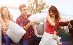 Amis gais jouant le combat d'oreiller, se reposant sur le divan Image stock