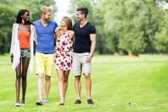 Amis gais marchant en parc et profiter d'un agréable moment Photos stock
