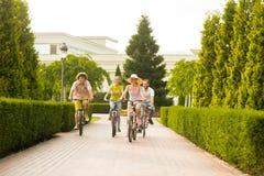 Amis gais montant des bicyclettes sur la route au parc Image libre de droits