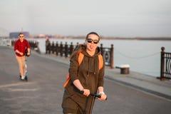 Amis gais montant le scooter de coup-de-pied Fille portant hoody vert-foncé avec le sac à dos orange et l'homme utilisant la chem Photos libres de droits