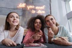 Amis gais observant le film passionnant à la maison Photo libre de droits