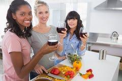 Amis gais préparant un repas ensemble et buvant du vin rouge Images stock