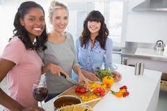 Amis gais préparant un repas regardant ensemble l'appareil-photo Photographie stock libre de droits