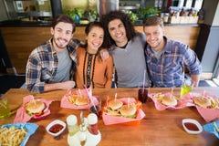 Amis gais prenant le déjeuner dans le restaurant Photographie stock libre de droits