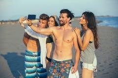 Amis gais prenant le selfie à la plage Image stock