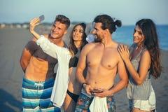 Amis gais prenant le selfie à la plage Photo stock