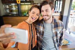 Amis gais prenant le selfie avec le mobile dans le restaurant Image stock