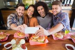 Amis gais prenant le selfie dans le restaurant Photos stock