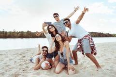 Amis gais prenant le selfie ensemble sur le smartphone sur la plage Photos libres de droits