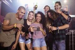 Amis gais regardant le téléphone portable dans la boîte de nuit Images libres de droits