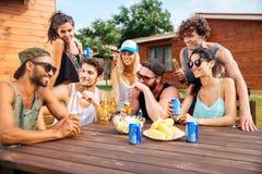 Amis gais riant et ayant la partie à la table dehors Photographie stock